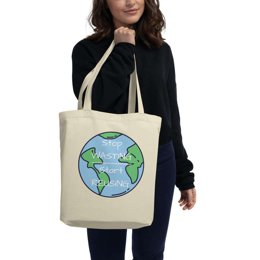 "A model wearing a black top and dark blue jeans holding onto a filled Oyster Stop Wasting, Start Reusing Tote Bag.  She is showing the front of the bag which has an image of the world and the words ""Stop Wasting, Start Reusing"" in the middle of the world."