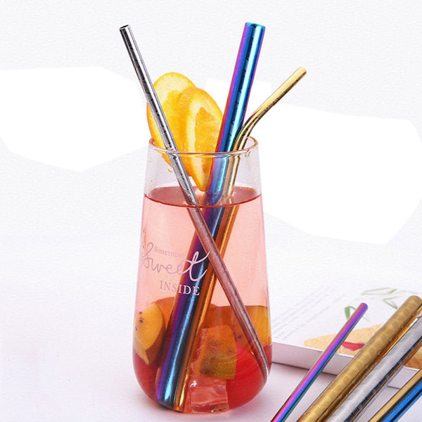 Glass cup with juice, fruit, & 3 of the stainless steel straws.  One thin, one curved, & one thick.