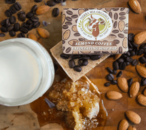 Almond-Coffee-Exfoliating-Soap-Bar-from-above-with-milk-honey-and-coffe-beans-on-wooden-board