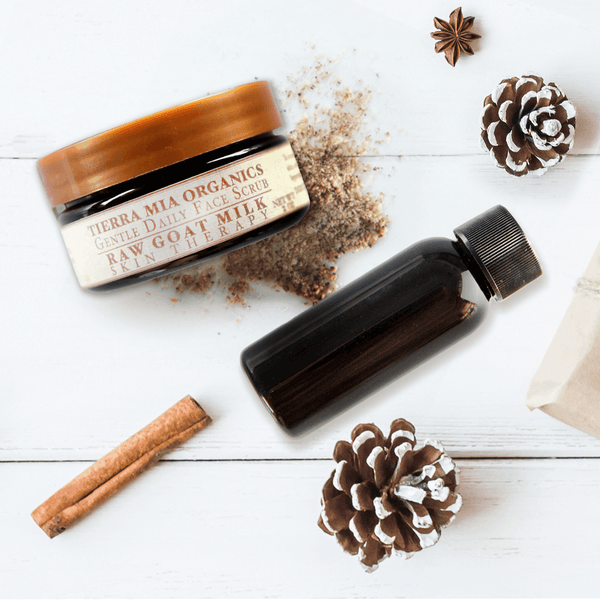 Tierra_Mia_Organics_Gentle_Daily_face_scrub_and_cleansing_oil_from_above_on_white_washed_wood_with_pinecone_and_cinnamon_stick