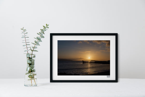 A black framed sunset photograph of The Blackrock Diving Tower at Salthill Beach Galway