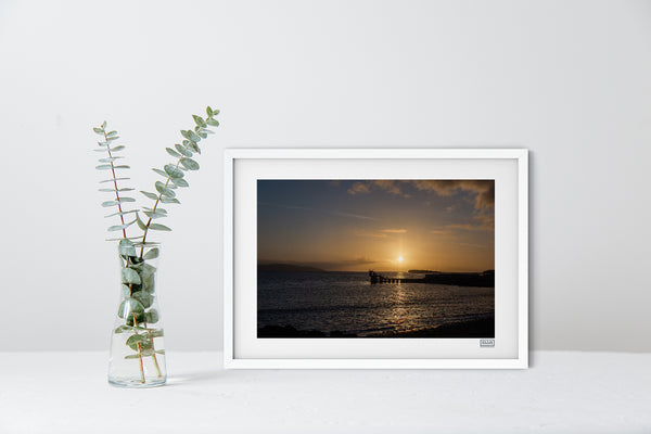 A contemporary white framed sunset photograph of The Blackrock Diving Tower at Salthill Beach Galway