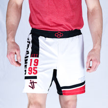 Load image into Gallery viewer, model wearing white, black, and red Jordan Trained Elite Wrestling Shorts. Established 1995
