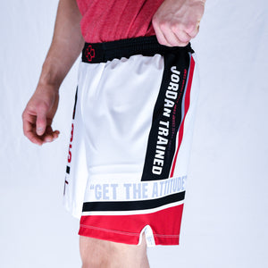 Side View of model wearing white, black, and red Jordan Trained Elite Wrestling Shorts.