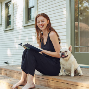 Girl sits on front porch with dog wearing cozy terry cloth one-piece.