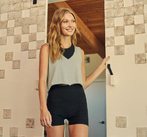 Model poses smiling in doorway in our new 3 inch running short