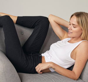Model lounges on couch in joggers.