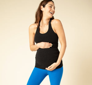 Maternity model posed in blue leggings and black tank