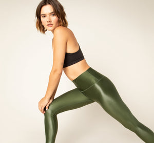 Model poses in high shine green legging and sports bra