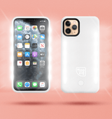 2 white floating iphone cases side by side and back to front. Case on the left has flashing lights either side of the case. Case on the right has a white Modzie logo bottom centre and a button below the logo with flashing lights either side of the case. Both cases have a black shadow under the cases and pink background.