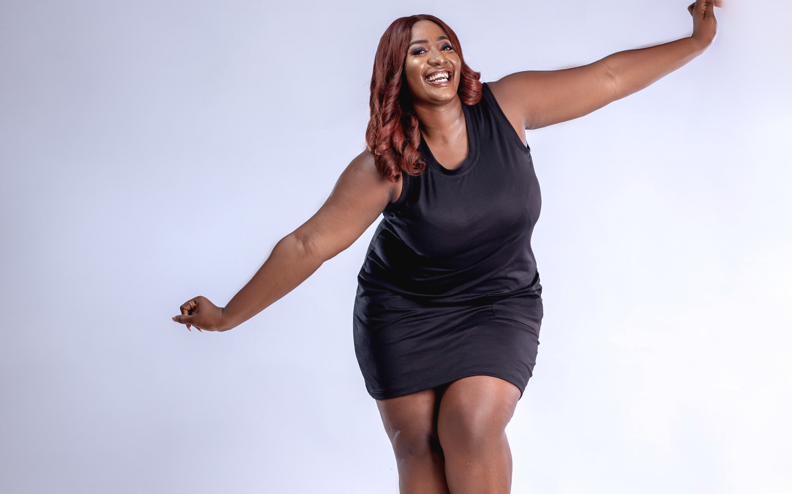 Dark skinned overweight woman with light reddish straight hair wears black suit stands smiling and happy with souls