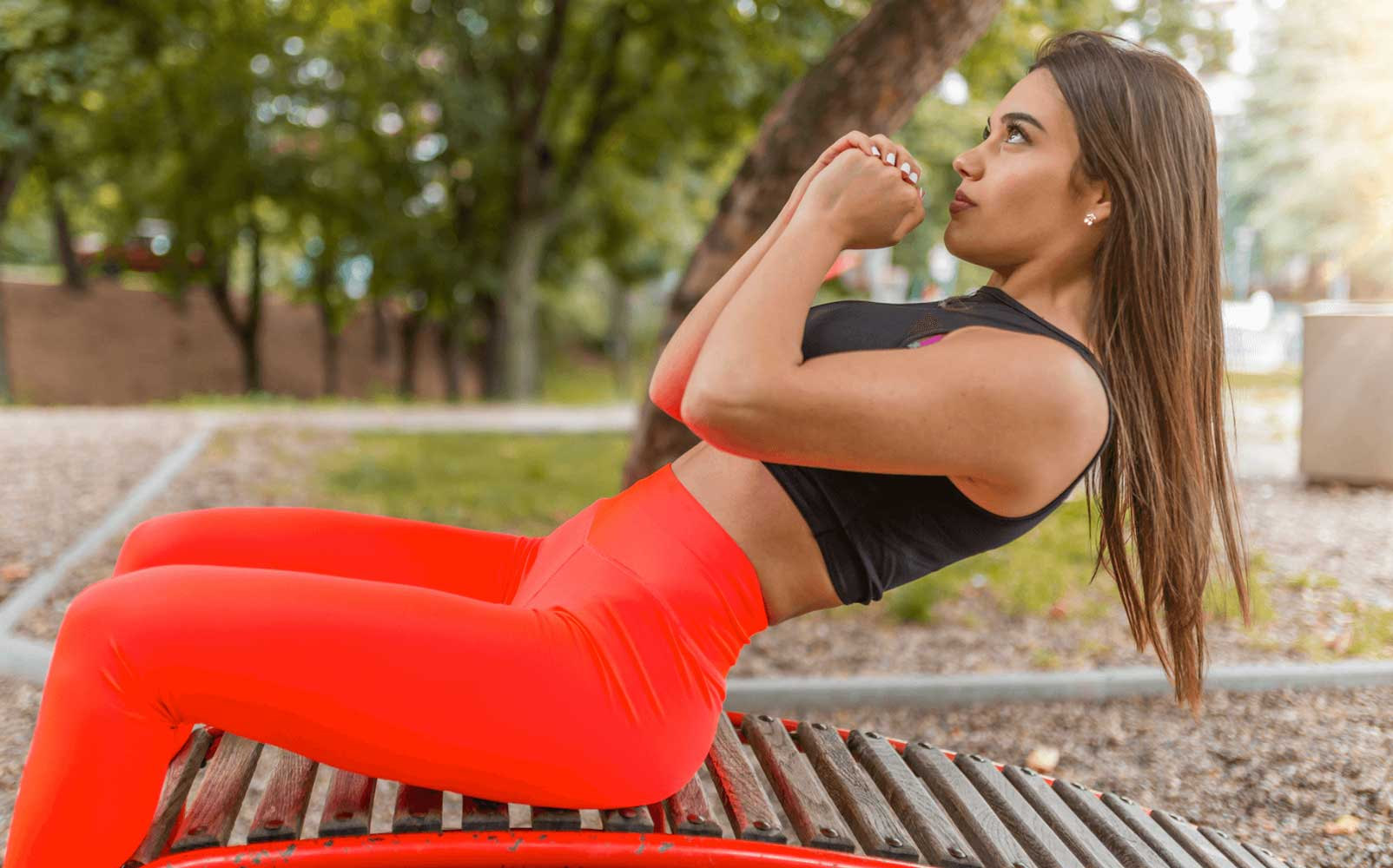 Young long-haired woman wears orange pants with crossed hands performing exercises to reduce adobmen looking fat-free outdoors