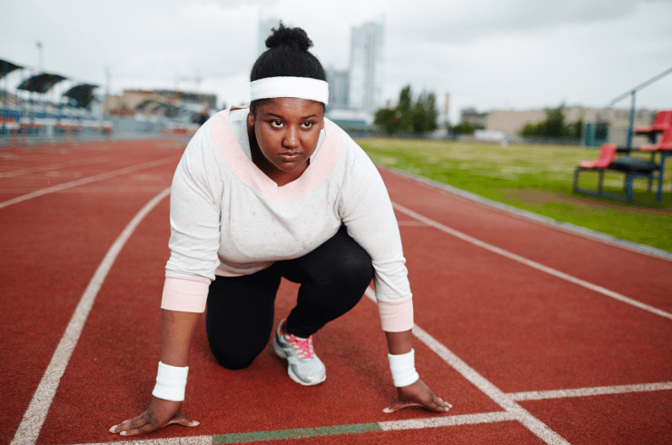 Young_african_american_woman_at_running_track_starting_line