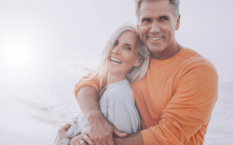 couple of smiling adult man and woman, the man has the woman hugged on his chest