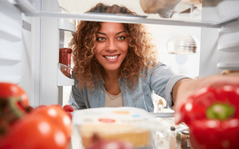 Smiling dark-skinned woman with curly hair light blue eyes at refrigerator door looking for healthy food