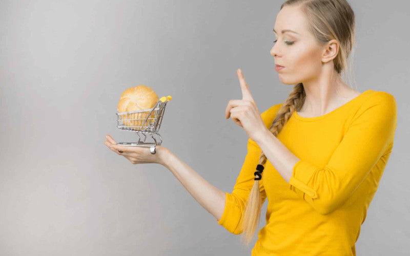 slim woman in one hand holds a market cart and the other hand points the finger saying no to gluten