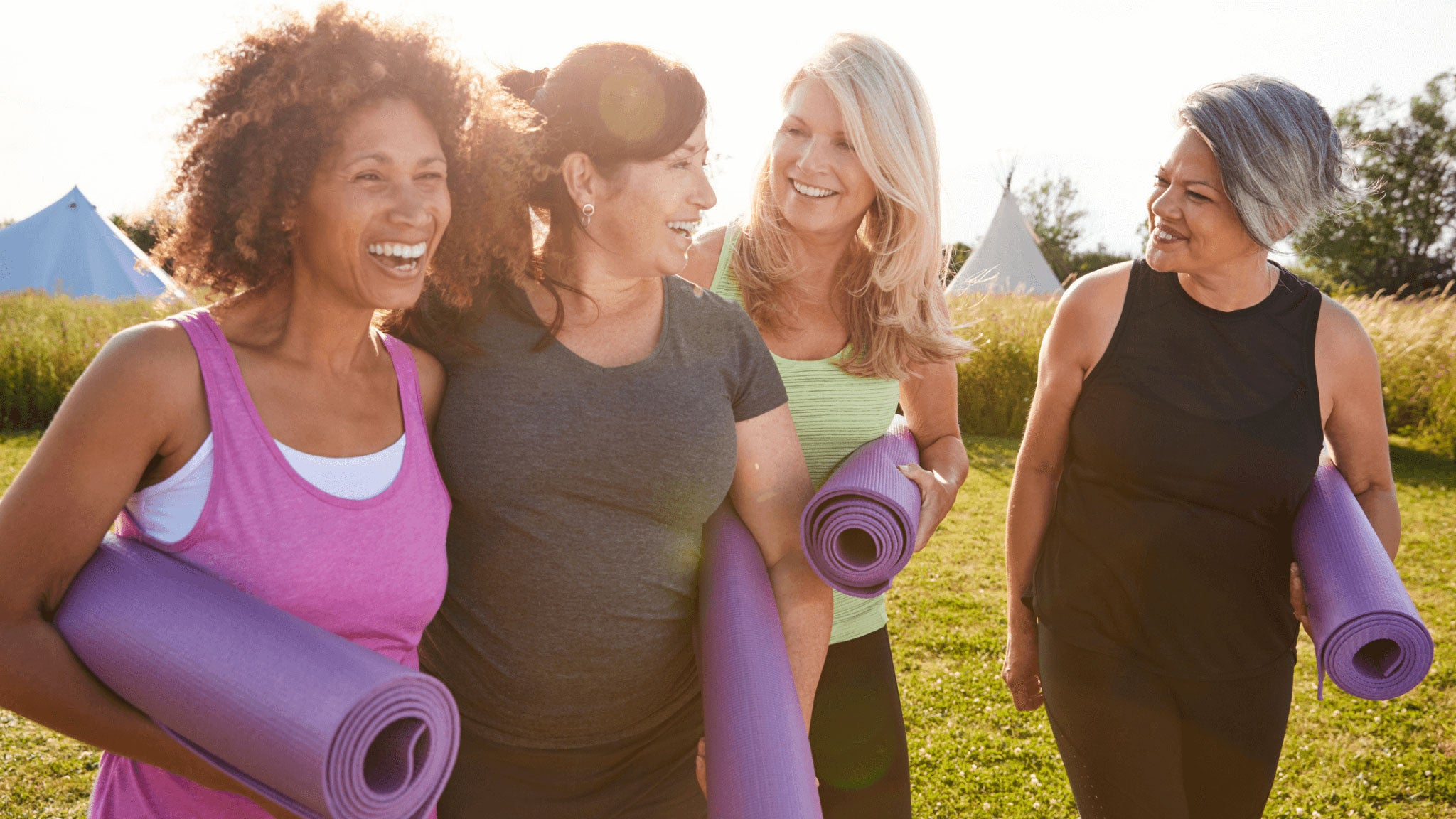 group of happy women outdoors with equipment for doing yoga