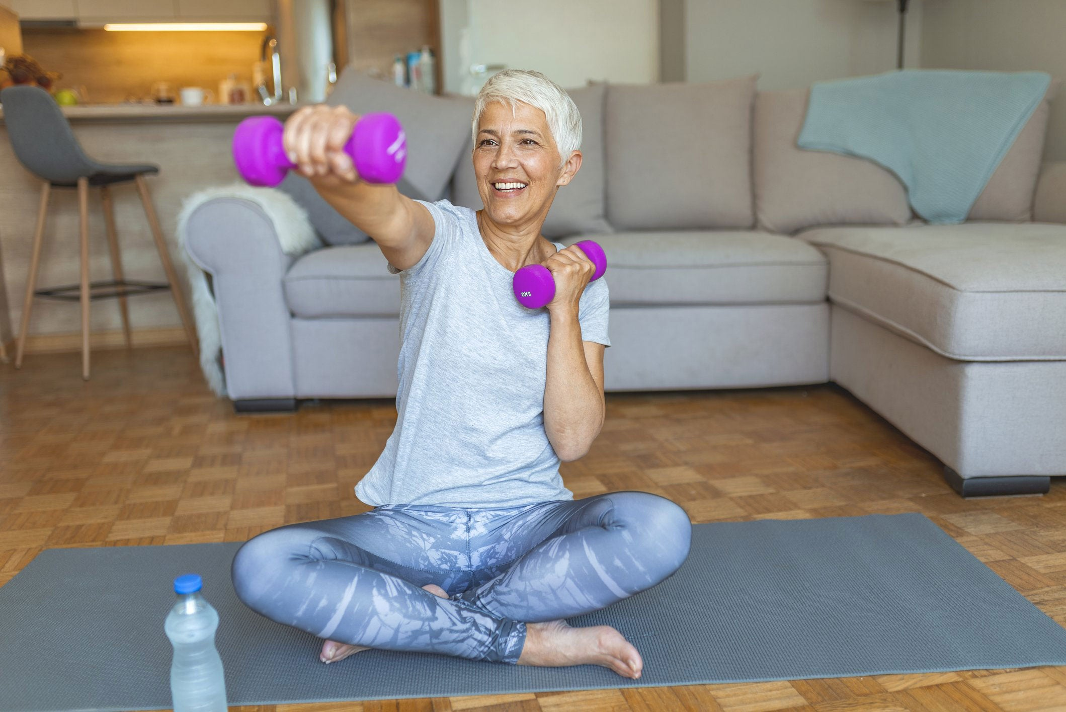 happy middle-aged woman exercising in living room at home