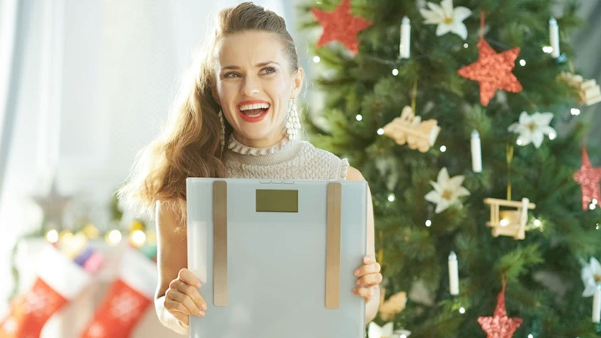happy woman holding a christmas gift scale with christmas tree in background
