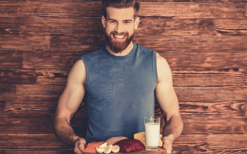 smiling young man hold in his hands a plate of healthy food