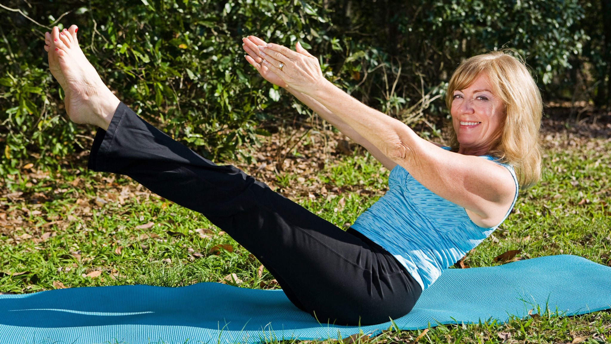 healthy woman doing yoga in a blue mat on a garden