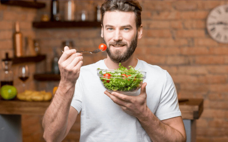 young man with fork in hand eating healthy salad