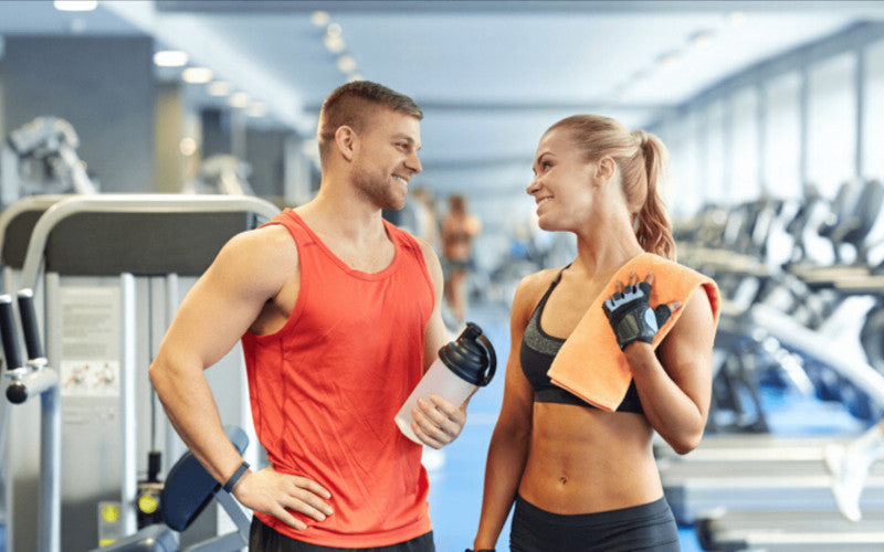 Young man and woman in good physical shape, the man holds a container of almased drink in his hands they look face to face in a gym