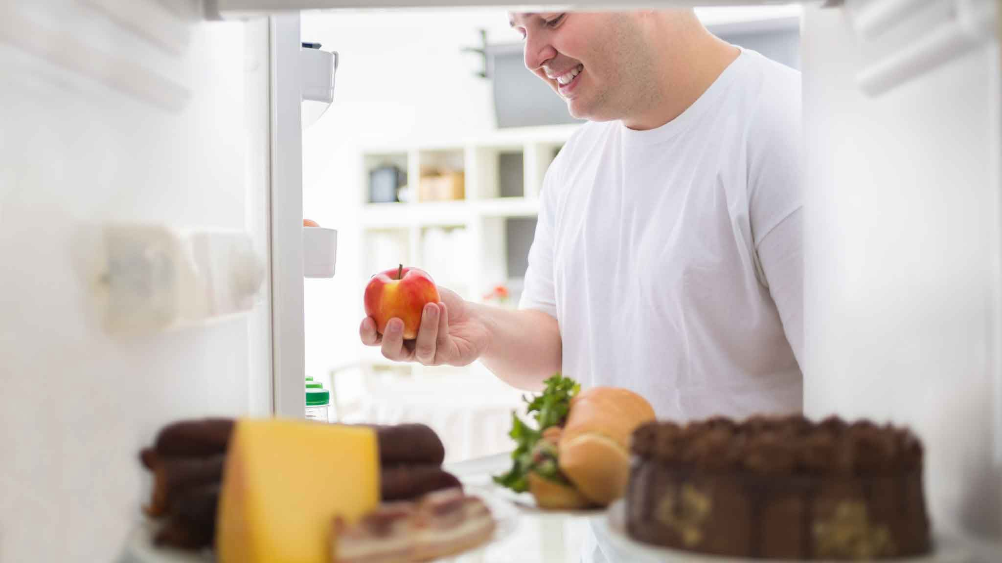 man in the fridge picking up an apple instead of candy and cakes