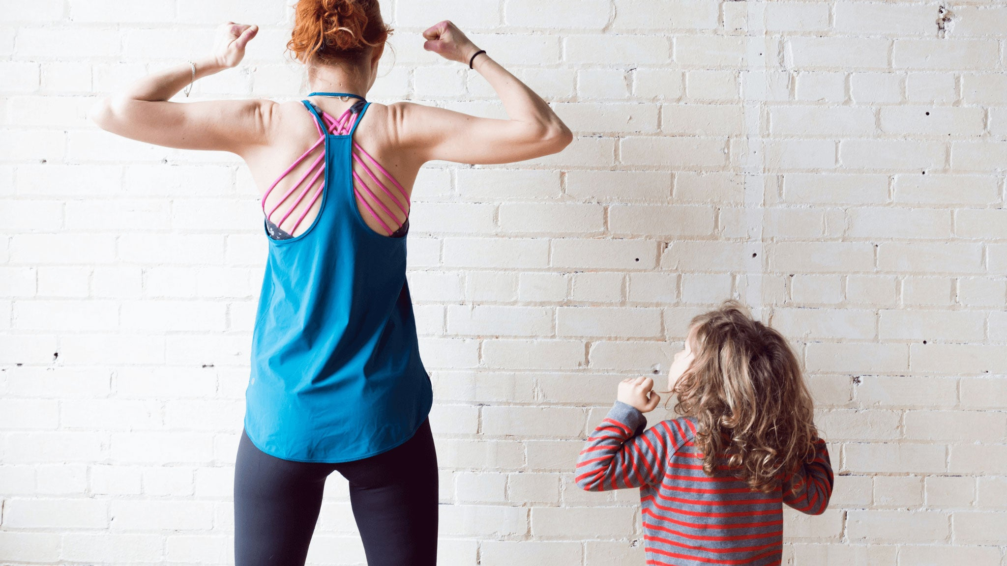 woman and girl wearing sportswear doing exercises on white brick wall background