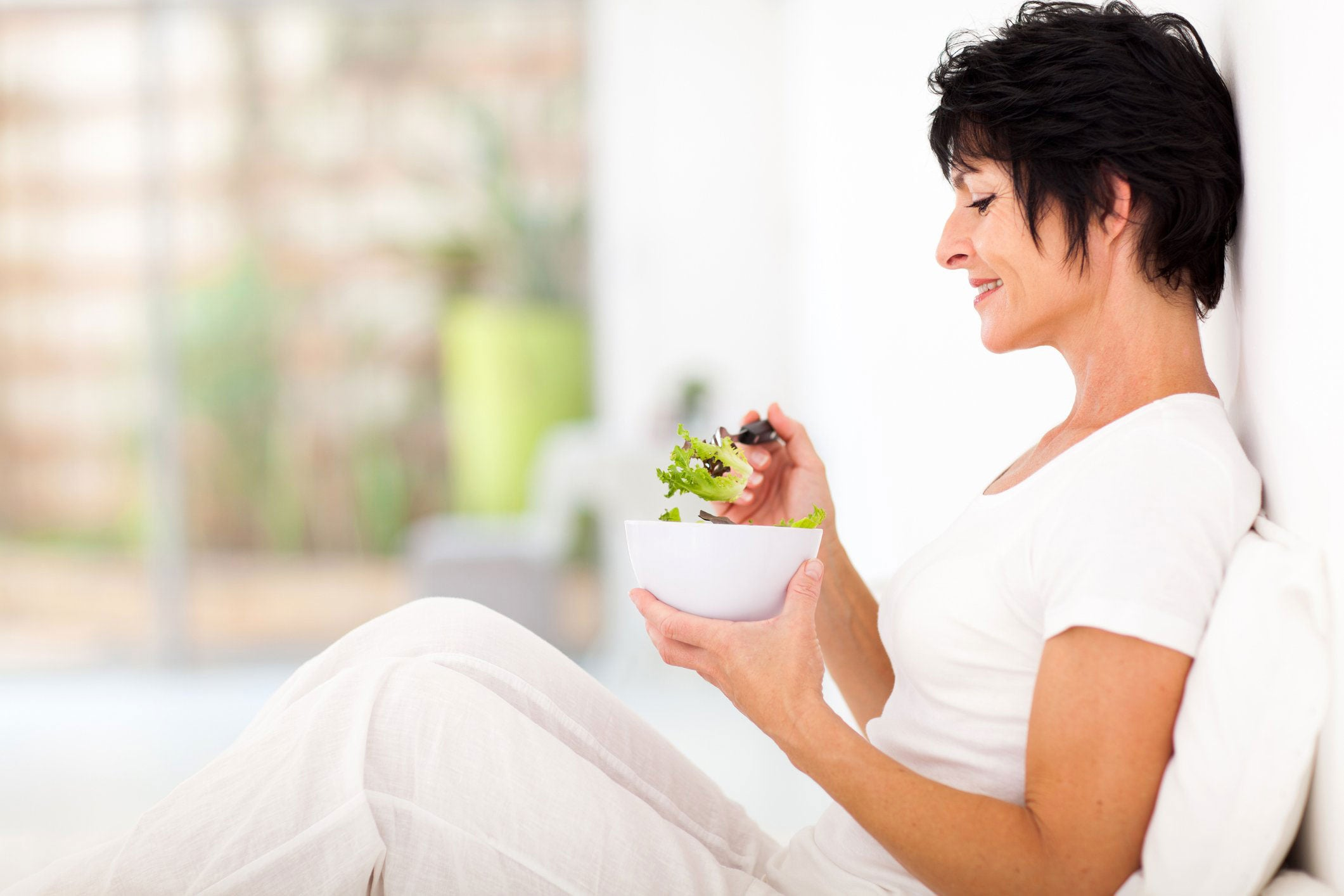 woman dressed in white sitting eating a bowl of salad