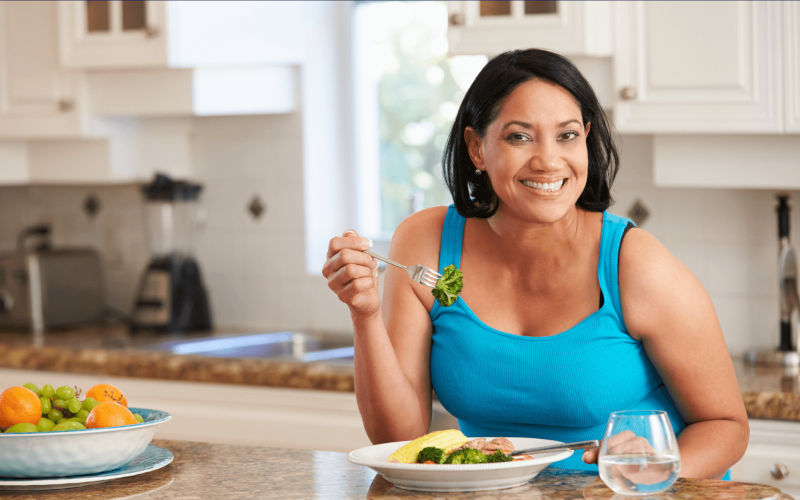 smiling adult dark-skinned woman sitting at a kitchen table with a fork in her hand eating broccoli