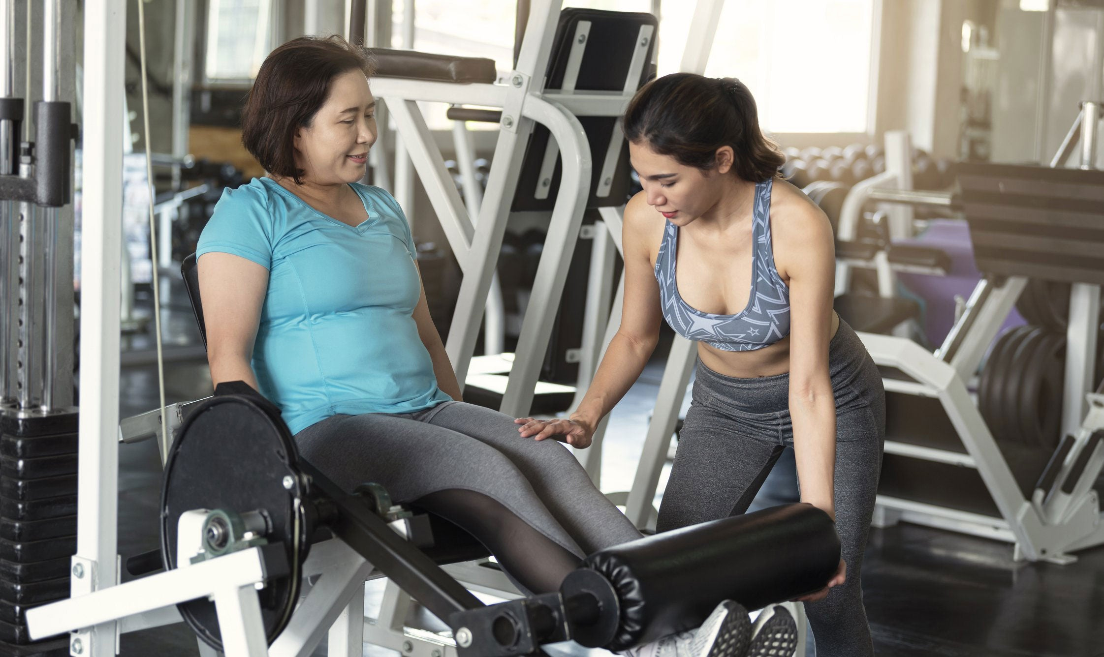 woman in the gym exercising with her coach