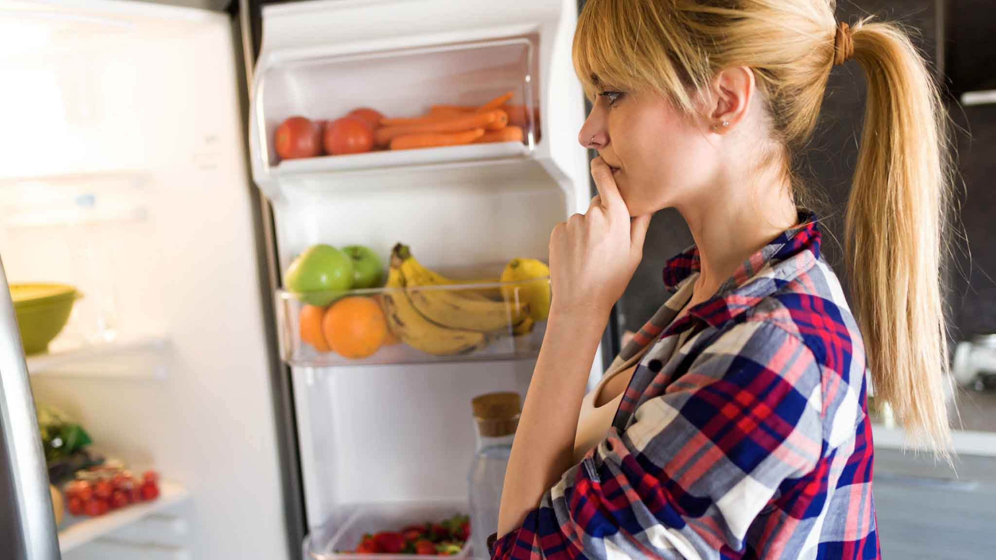 woman in the refrigerator wondering what to eat and the refrigerator is full of healthy food