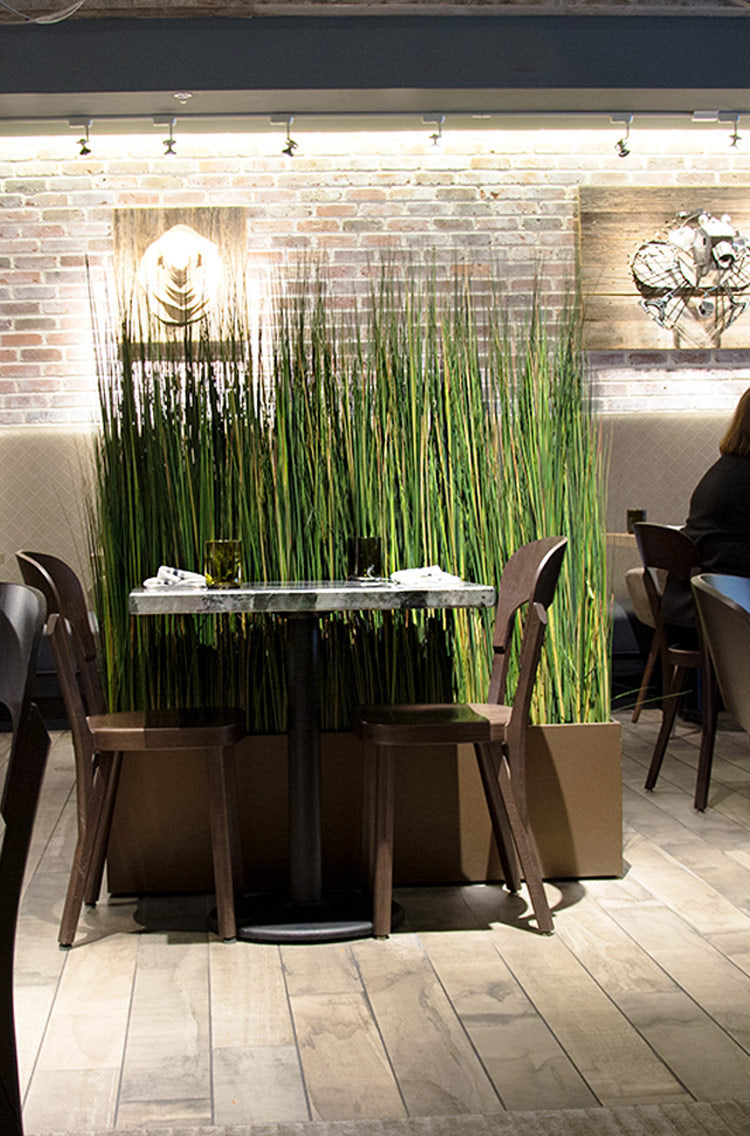An example of creative social distancing barrier design in a restaurant utilizing permanent botanicals and locally-made planters.
