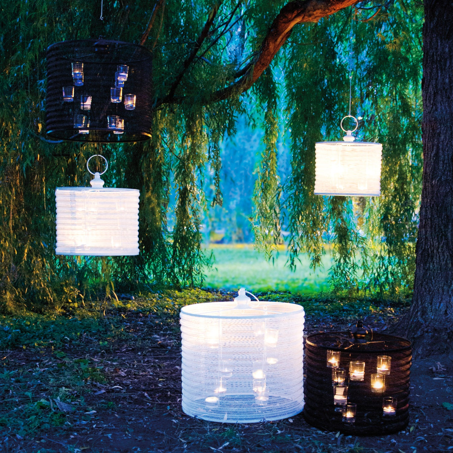 White and black Aria Candle Chandeliers in a moody weeping willow tree setting.