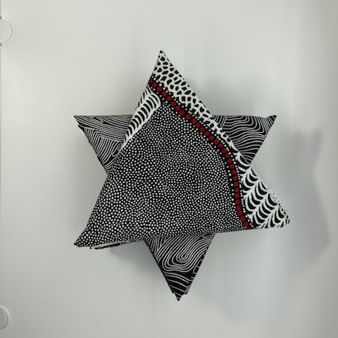 The picture shows a carefully curated selection of black, white and some red Australian Aboriginal fabrics, nicely arranged into a star.