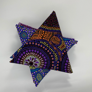 The picture shows a carefully curated selection of purple Australian Aboriginal fabrics, nicely arranged into a star.