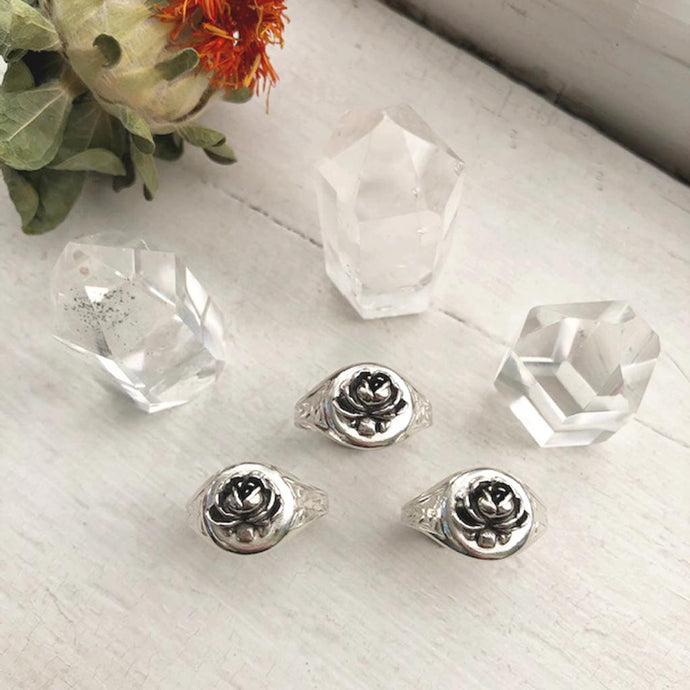 three rose signet rings displayed with three crystals