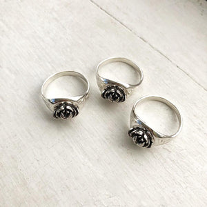 three silver rose signet rings on white window sill