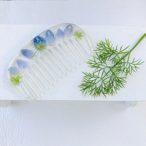 hair comb with blue flowers on white next to a piece of dill