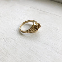 Load image into Gallery viewer, side view of brass signet ring with rose in center on a white window sill