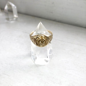 yellow brass signet ring with rose displayed on clear crystal