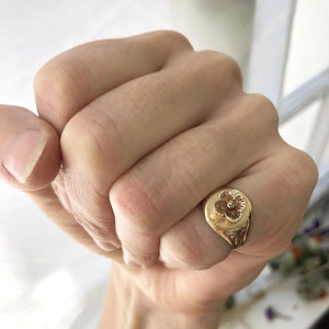 yellow flower signet ring on pinky finger making a fist