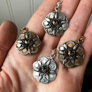 hand full of floral pendant necklaces