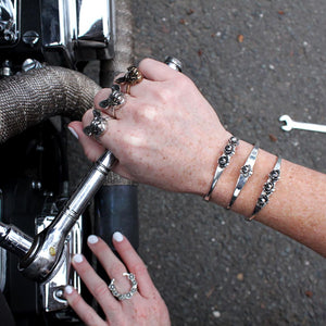 two hands fixing Harley Davidson with handmade sterling silver jewelry