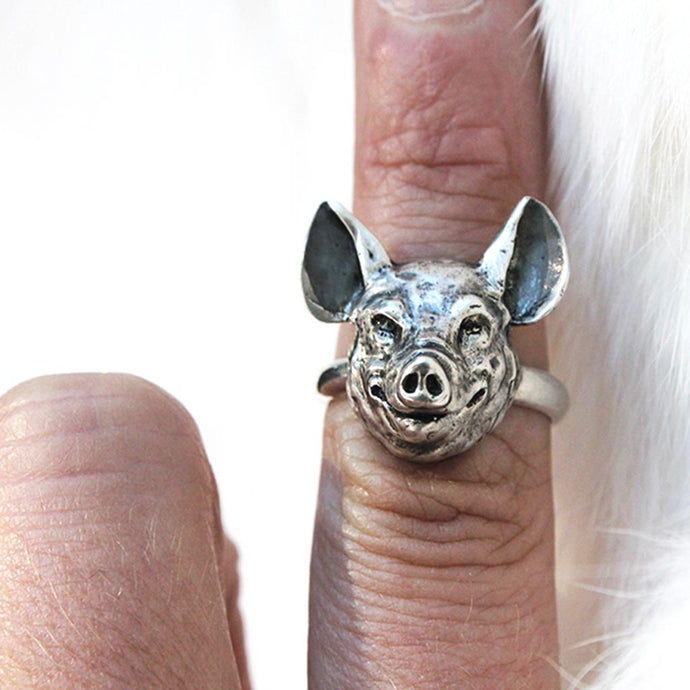 silver pig head ring on a finger