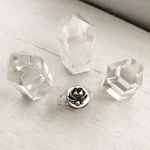 one sterling silver rose signet ring displayed by surrounding crystal towers on white background