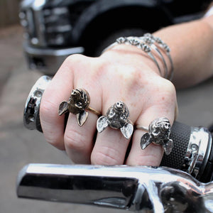 three pig rings on hand holding throttle on Harley Davidson motorcycle