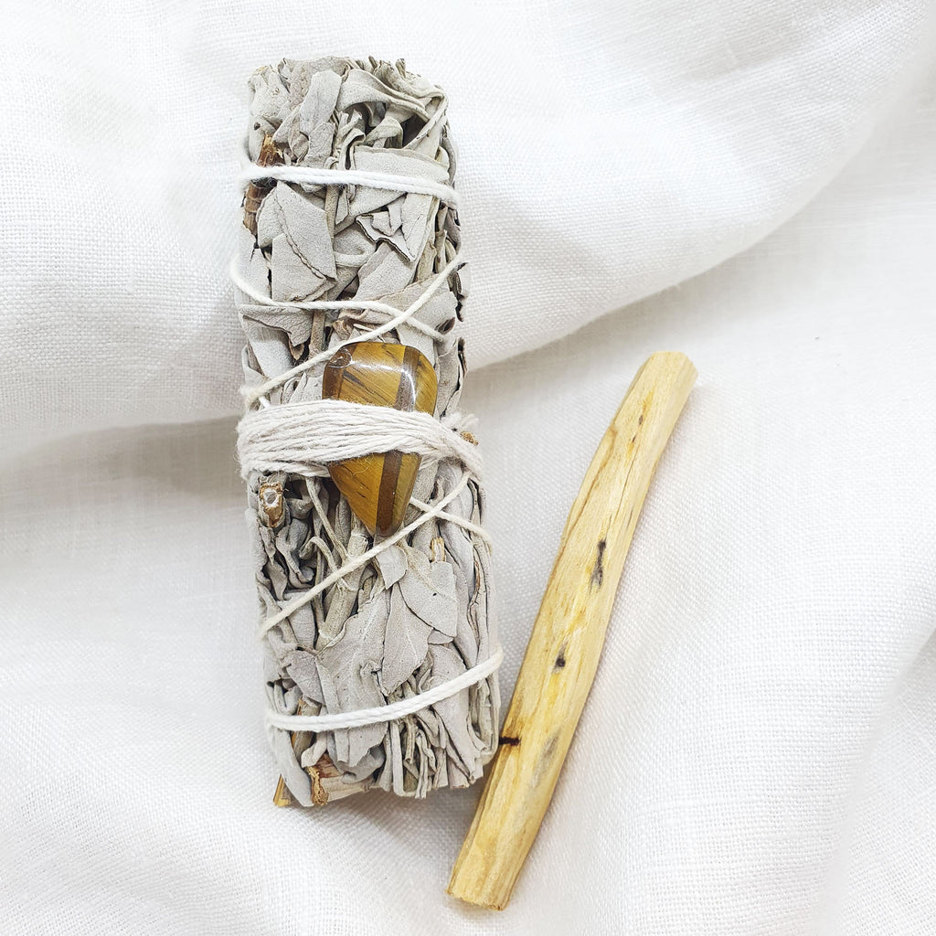 white sage smudge stick and palo santo with tiger's eye