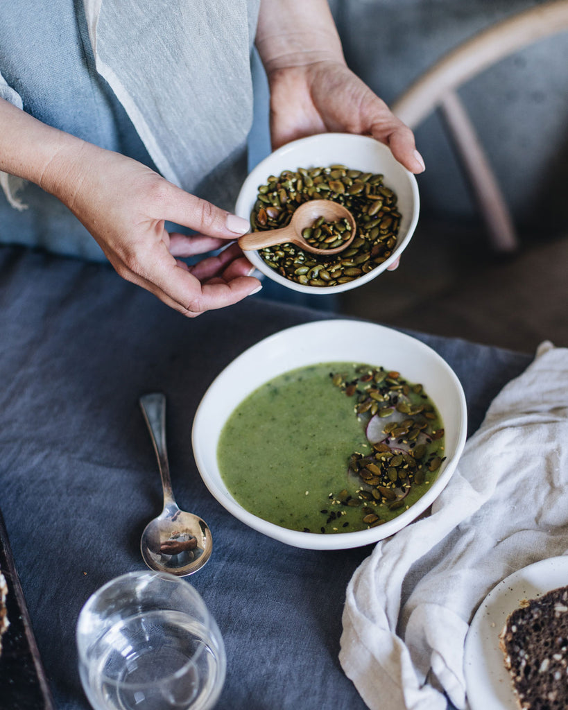 Winter pea and mint soup, sprinkled with pepitas in a stoneware handmade bowl